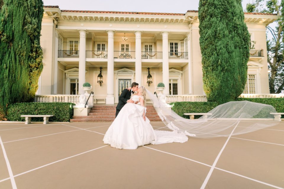 a groom dips his bride at their Grand Island Mansion wedding