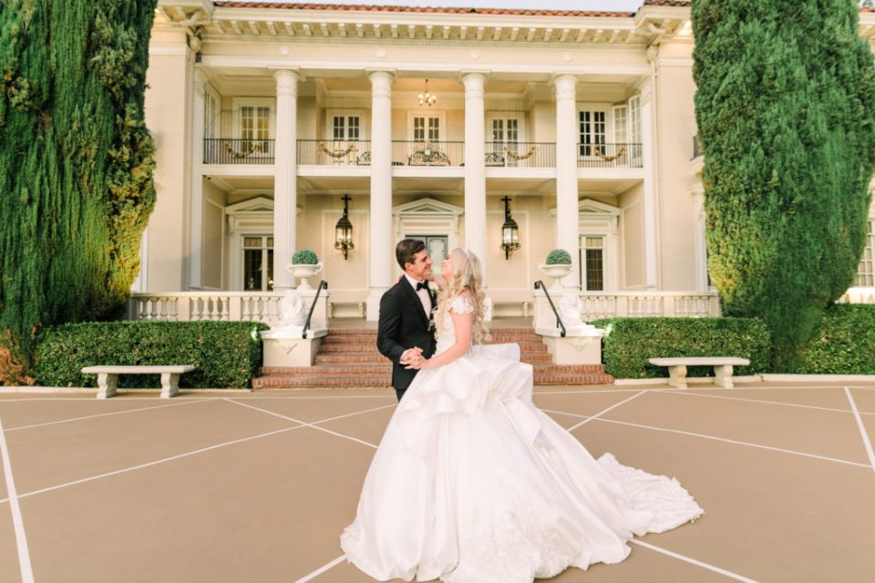 a couple laughs and kisses during photos at their Grand Island Mansion wedding