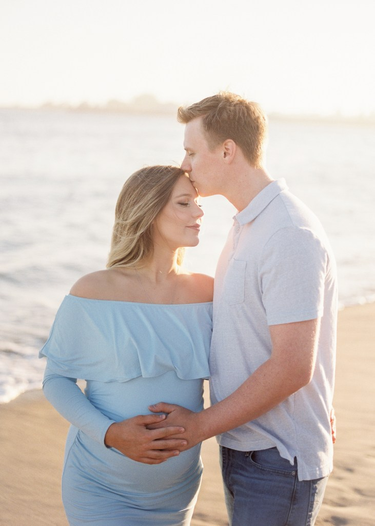 husband and wife have maternity photos at the beach for tips for beach photos