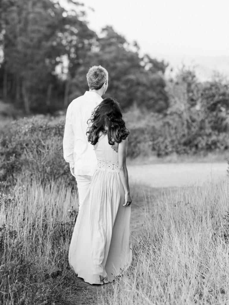 a black and white photo of a couple walking through the prairie during their Marin County engagement photos