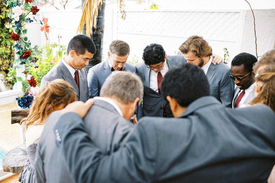 a groom and his groomsmen pray before a Bay Area intimate wedding