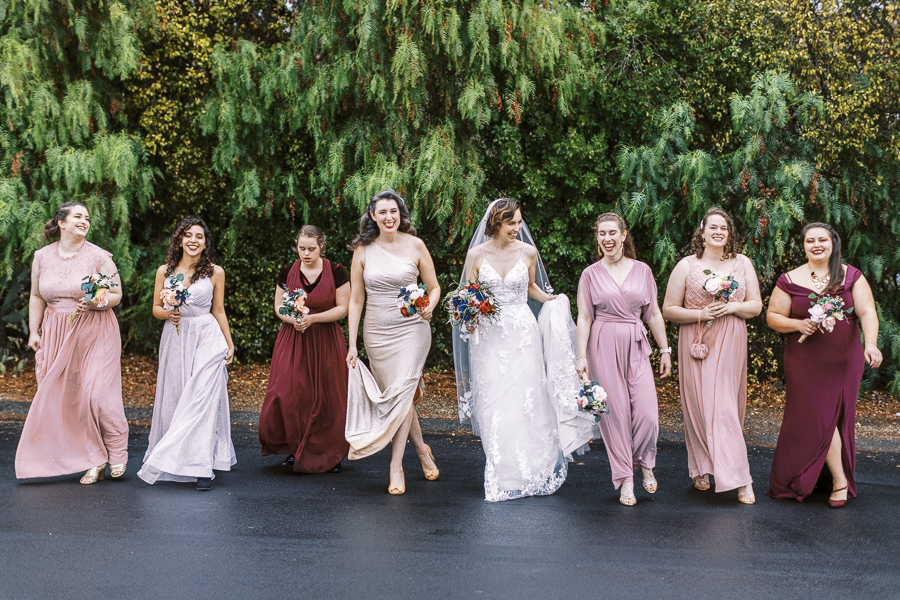 a bride and her bridesmaid walk and laugh before a Bay Area intimate wedding