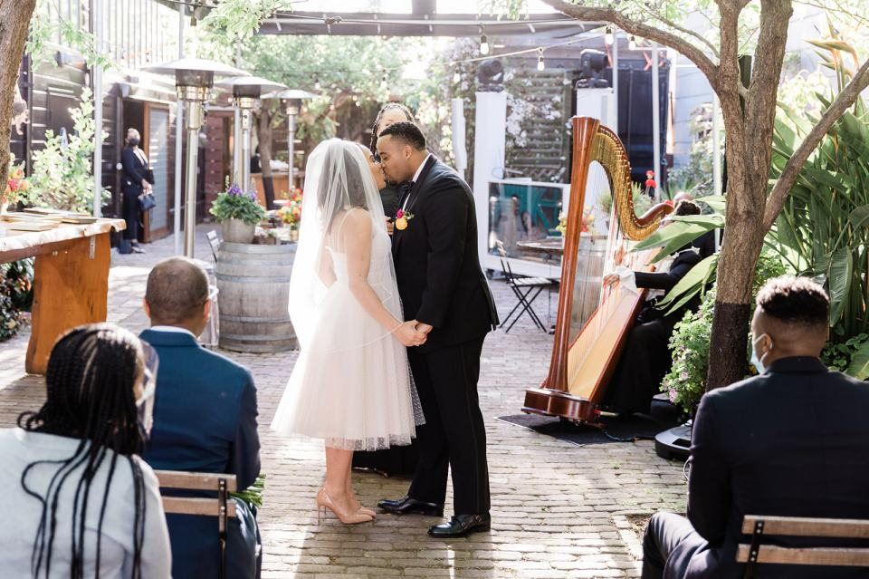 a bride and groom share their first kiss at their wedding at Stable Cafe in San Francisco