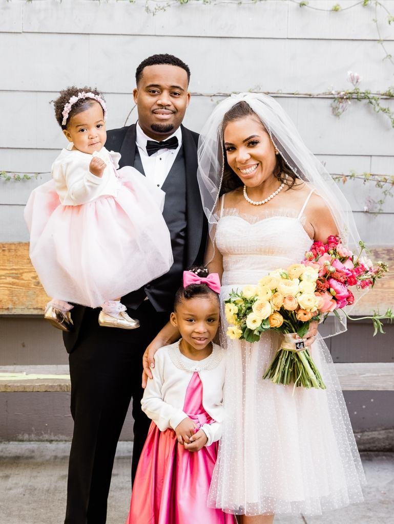 a bride and groom pose with their daughters for a photo at Stable Cafe in San Francisco
