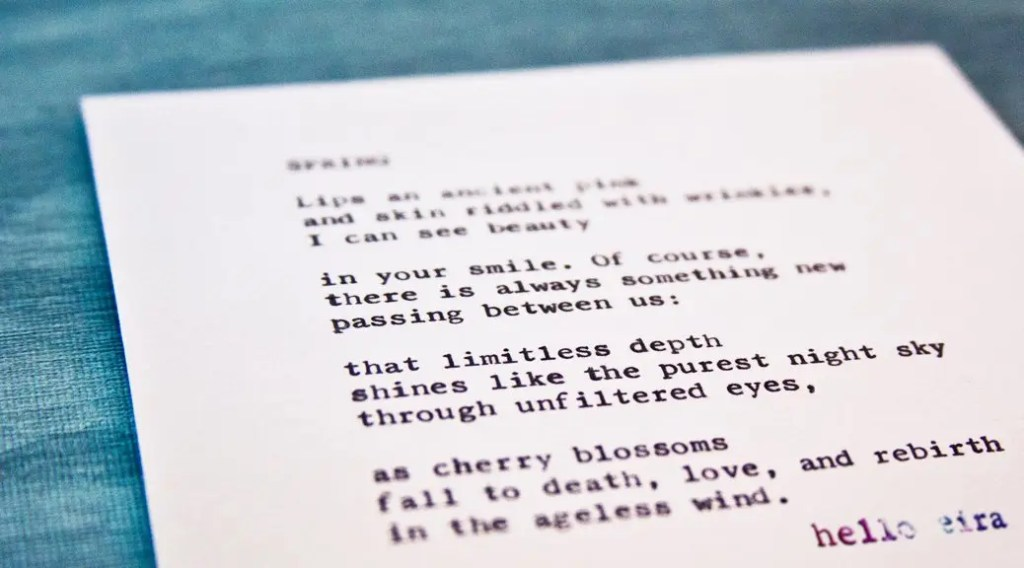 "Etsy Typewriter Poetry Poem ""Spring."" Dutch angle against blue wood card stock. Watermark: hello eira"