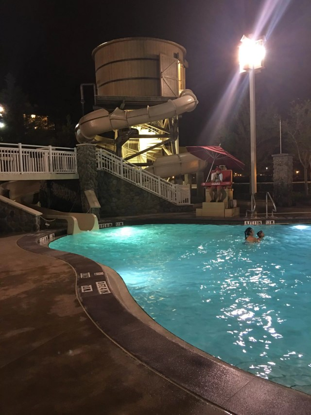 A tall pool slide with a tower at night at Saratoga Springs Resort.