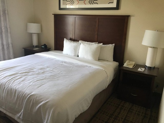 A king bed with a dark wood headboard and white comforter with four white pills with two side tables and a white lamp and shade on each.  An alarm clock on the left table and a telephone with a note pad on the right.
