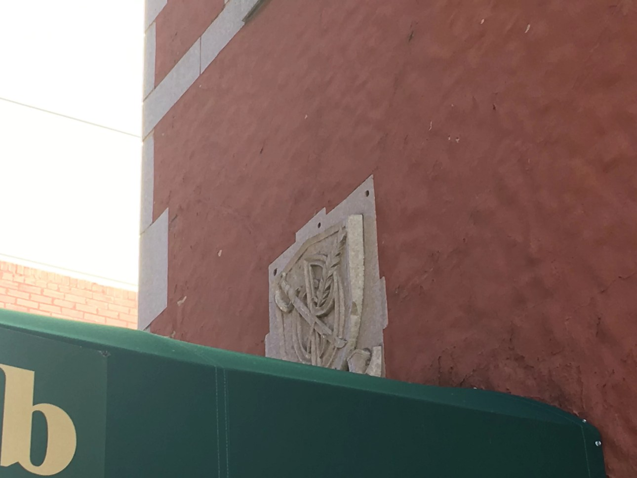 Denver press club coat of arms in stone above the green canopy