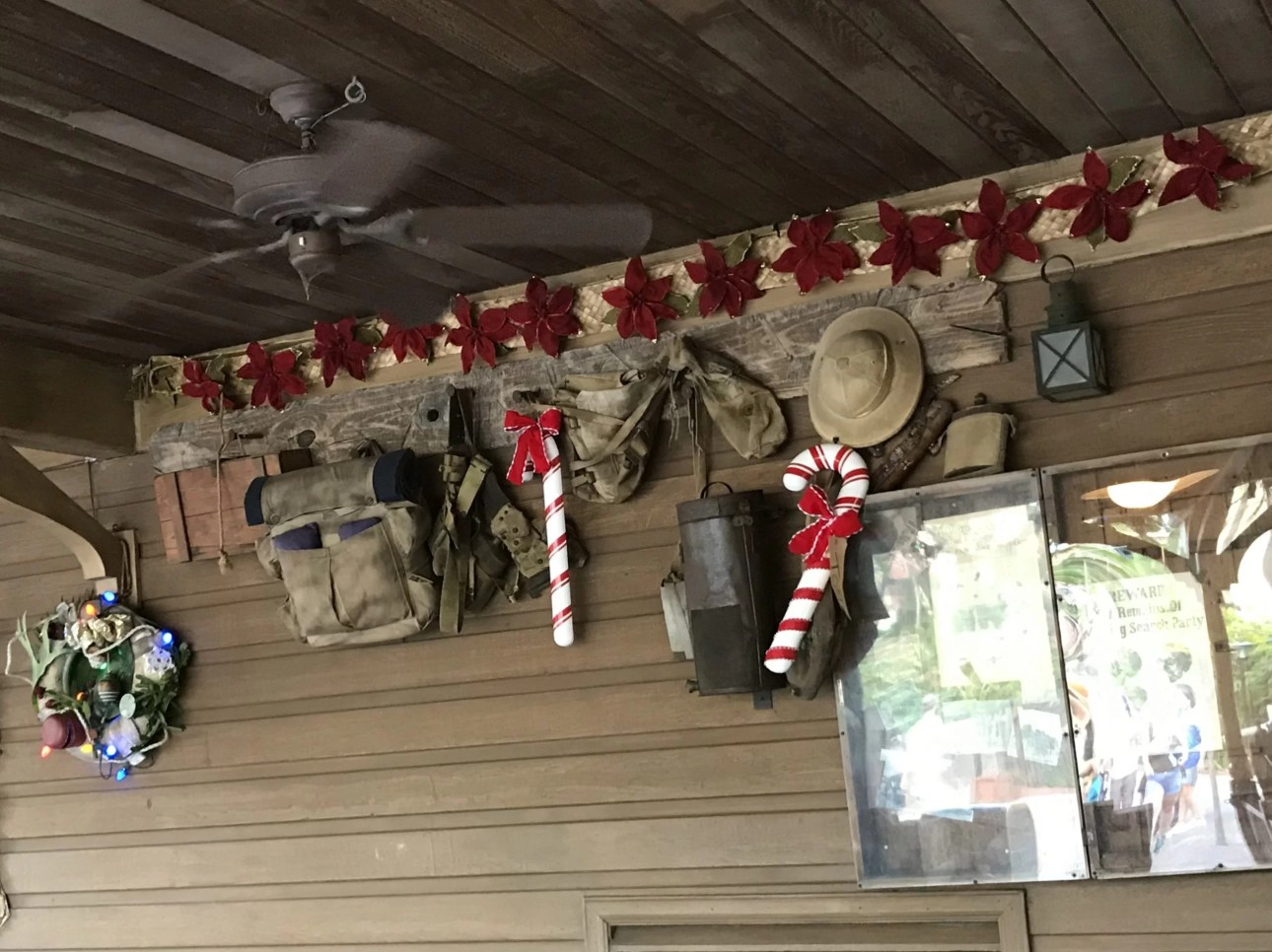 candy cane, wreaths, and poinsettias adorn the walls of the Jingle Cruise (Jungle) queue during Christmas