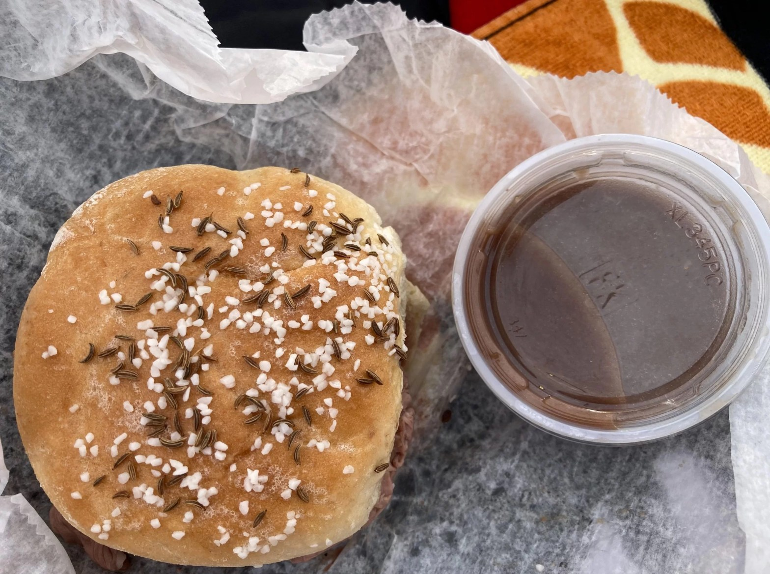 Kummelweck roll with roast beef and au jus on wax paper from Adri