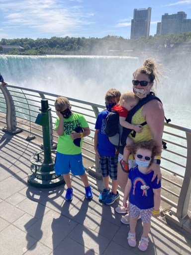 Three children and one women wearing a baby in front of the Horsehoe Falls in Niagara Falls