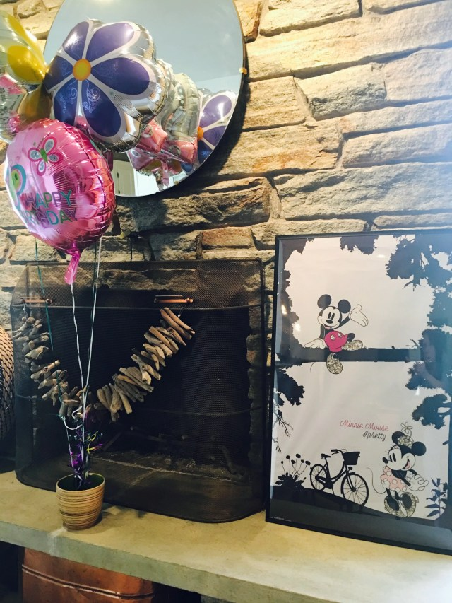 Three balloons and a minnie & mickey poster by a fireplace