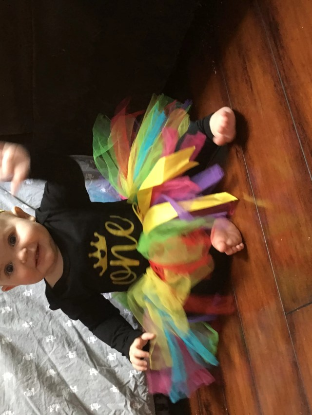 A redhead baby in a rainbow tutu, gold headband, and black t-shirt with 'one' waving