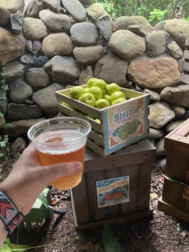 Glass of Apple cider in fromt of box of Granny Smith apples at appleseed  orchard in epcot