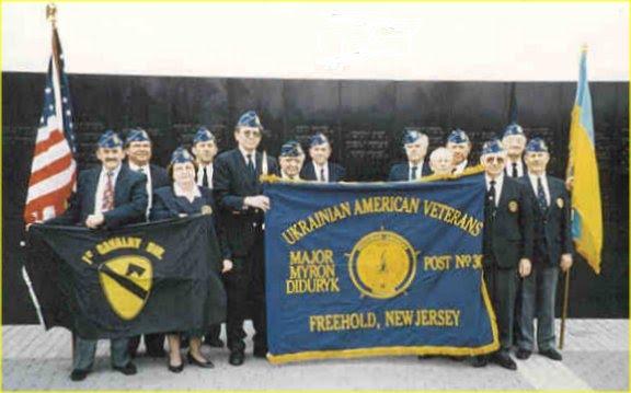 Ukrainian American Veterans (UAV) Post 30 members holding post flag at tribute to their patron, Major Myron Diduryk, at the inscription of his name on the New Jersey Vietnam Veterans Memorial in Holmdel, NJ