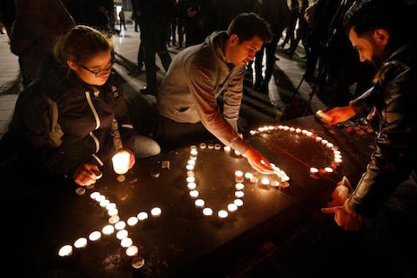 <p>People light candles in the shape of a cross and heart in Place de la Republique in Paris on Nov. 14. (Photo by Paul Haring/CNS)</p>