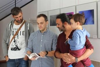Los tres fotógrafos ojean el catálogo de la muestra