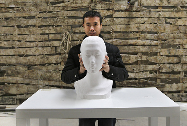 Chinese artist Li Hongbo shows his paper sculpture work, which is made of 6000 pieces of paper, on the outskirts of Beijing