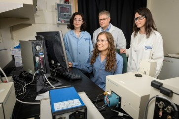 UD Professors Emily Day (right) and Joel Rosenthal (middle, back) have combined efforts to improve existing light-activated cancer treatments. Graduate student Andrea Potocny (seated) and undergraduate Rachel O'Sullivan (left) have helped with the research.