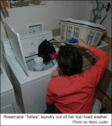 Rosemarie uses a reacher to get laundry out of a upright washer