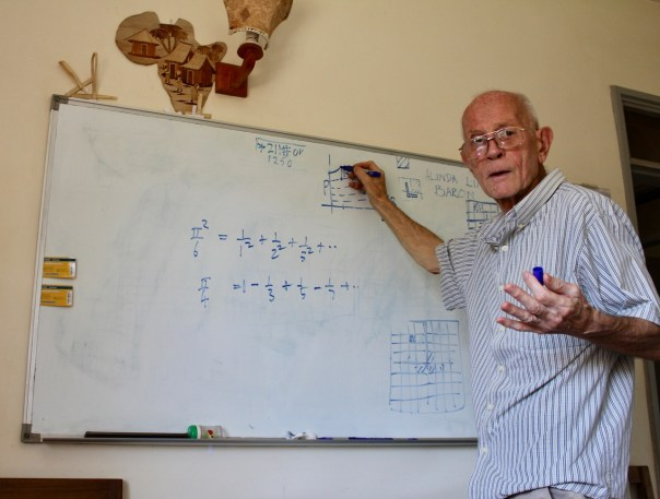 Dr. John Smith working a math problem on the white board in his UCU Tech Park apartment (UCU Partners photo)