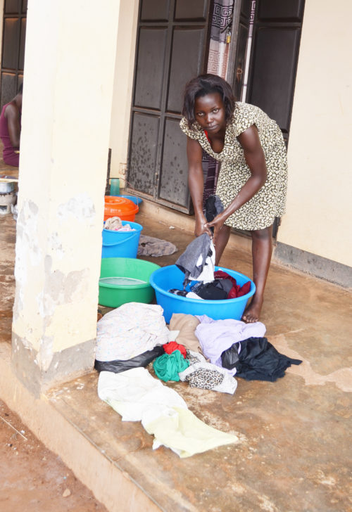 Justine Nanyanzi washes clothes at her residence