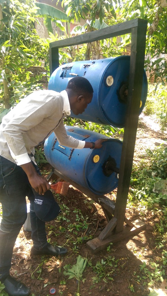 Inspecting the double-decker plastic composter after installation (UCU Partners photo)