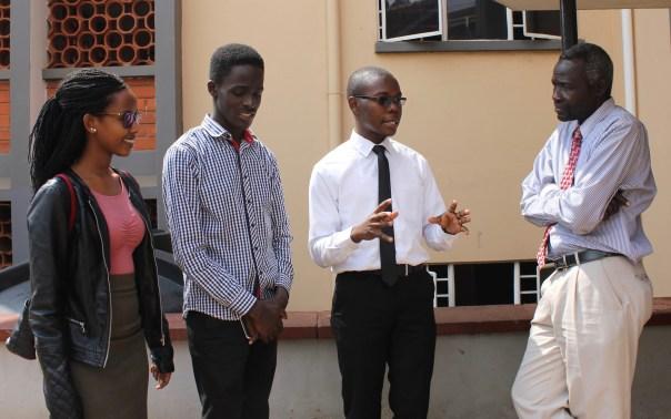 UCU School of Medicine (SoM) students Joana Bideri, Ronnie Mwesigwa and Peter Kabuye talk with Dr. Arabat Kasangaki, dental surgeon and lecturer at UCU's SoM at the Mengo Hospital, Kampala, Uganda.