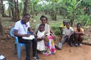 John Damasen Ntwari, president of the UCU Nursing Class of 2020, visits with a family in a remote village near Mukono.