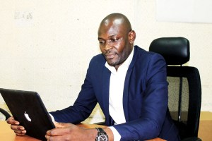 Simon Mwima working in the UCU Department of Social Work and Social Administration staff boardroom