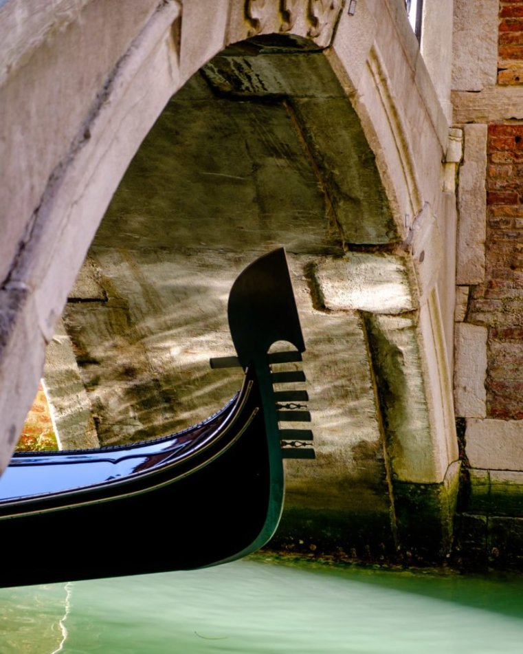 Detail of the bow of a gondola passing under a bridge, Venice