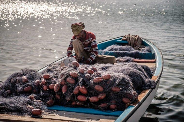 Fisherman repairing nets in Sur, Oman