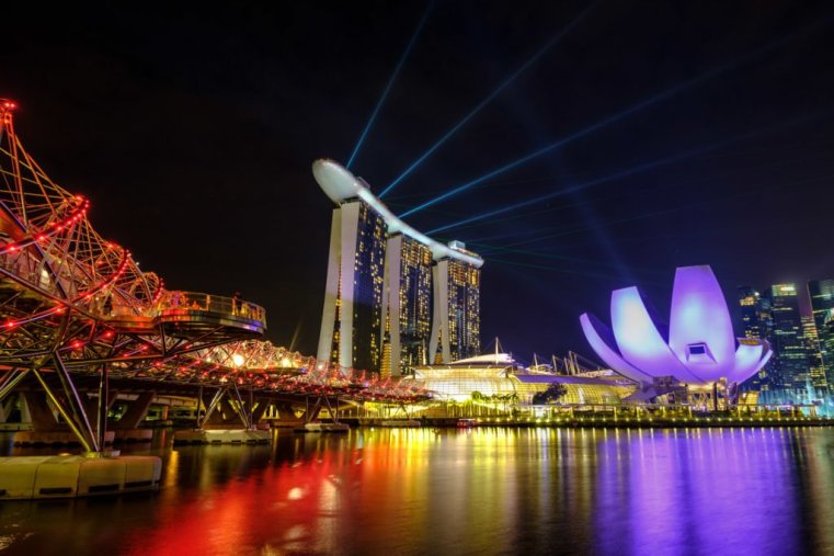 Marina Bay, Singapore at night with lasers shooting out of the Marina Bay Sands hotel