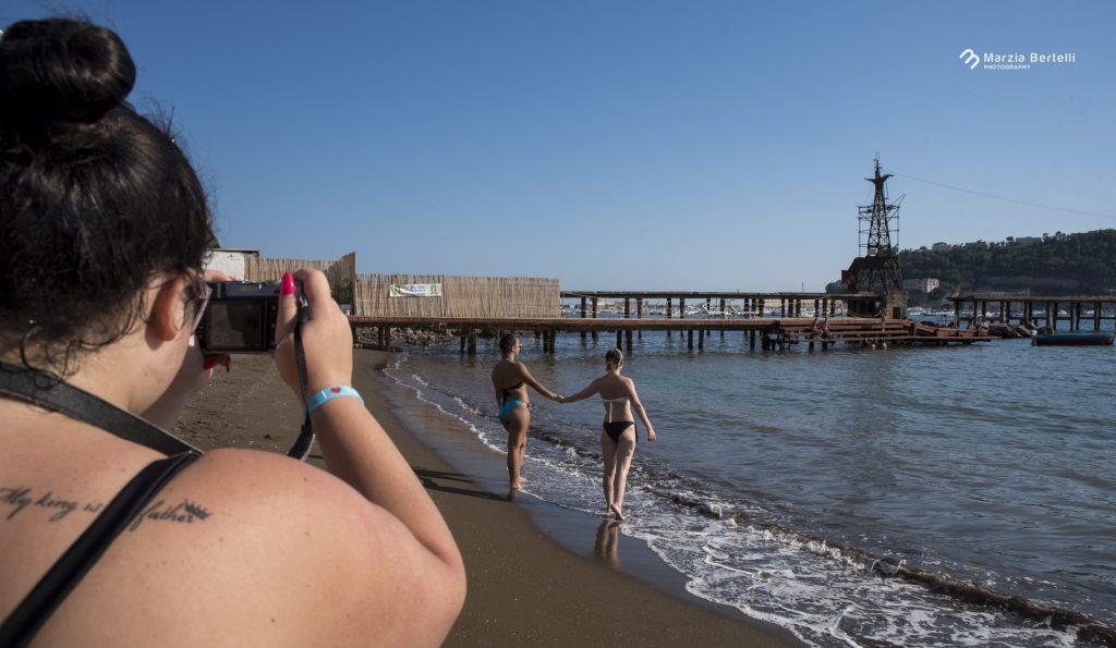 In spiaggia all'Ilva, Rosa di spalle fotografa Ania e Sara in riva al mare.