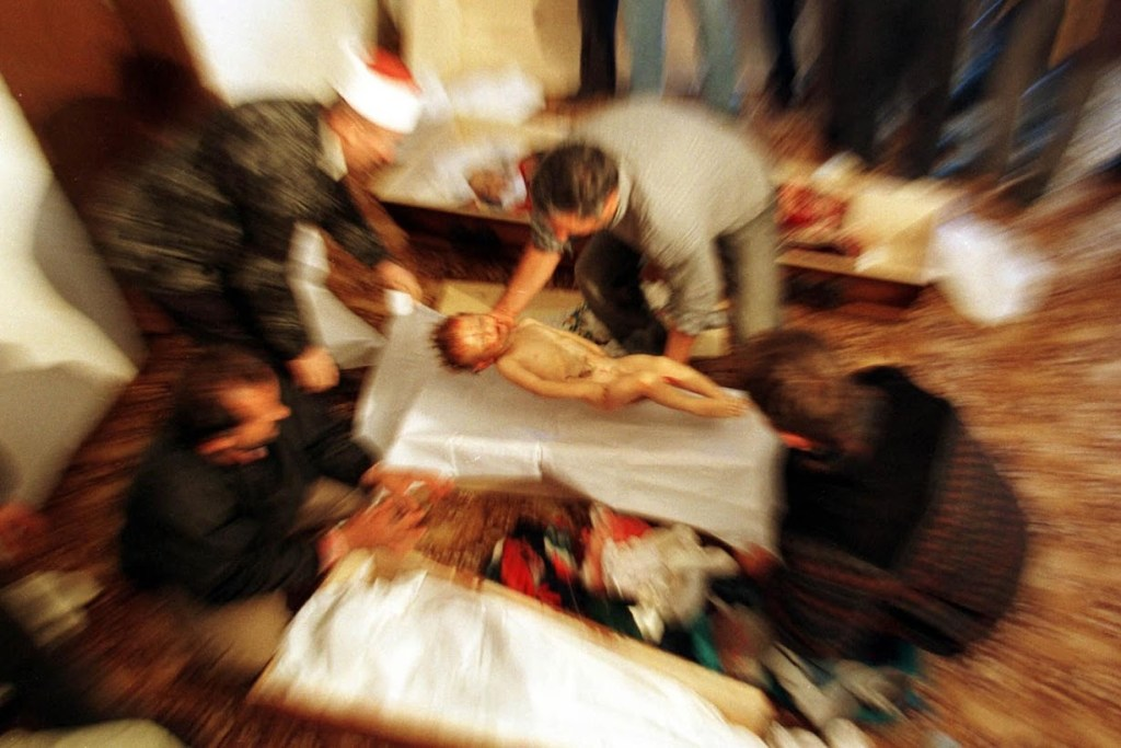 An ethnic Albanian man places the body of two-year-old Mozzlum Sylmetaj into a coffin next to the coffins of three other family members killed by Yugoslav army troops as they were crossing into Kosovo from Albania