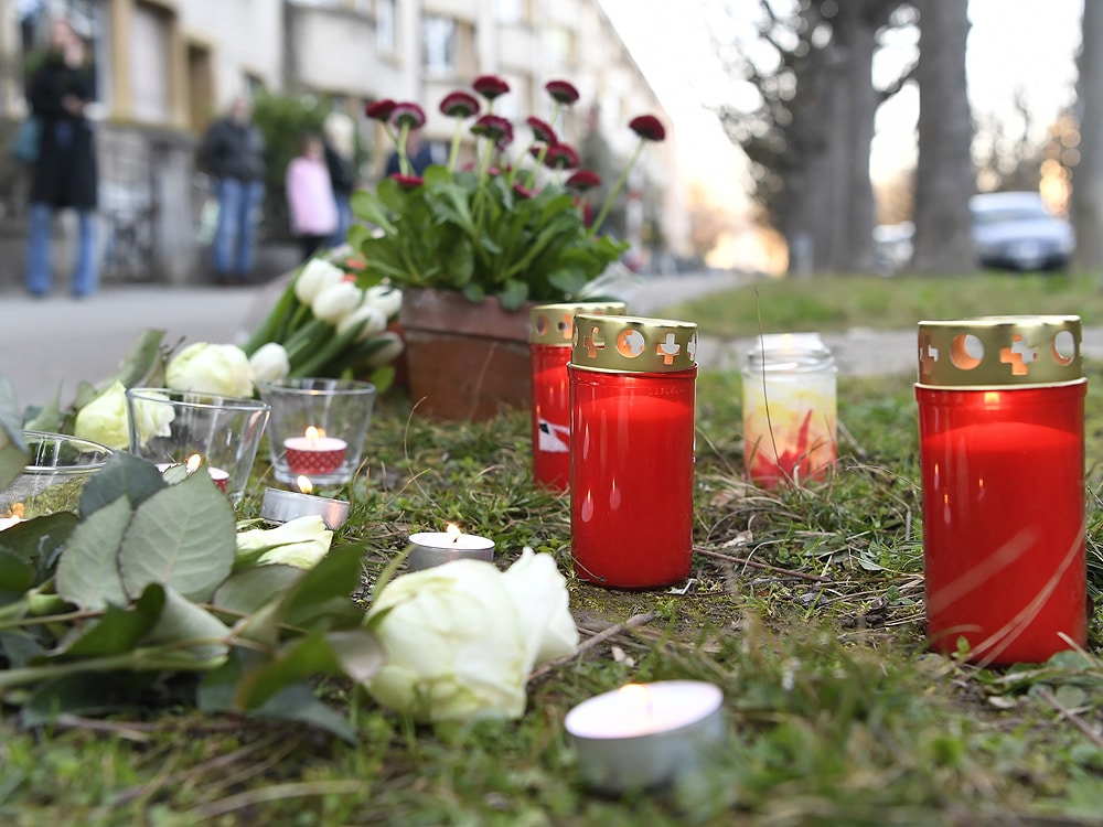 Flowers lay on the sidewalk where a 7-year old boy was stabbed on his way back from school in the Sankt Galler Ring area of Basel, Switzerland, Thursday March 21, 2019. (Georgios Kefalas/Keystone via AP)