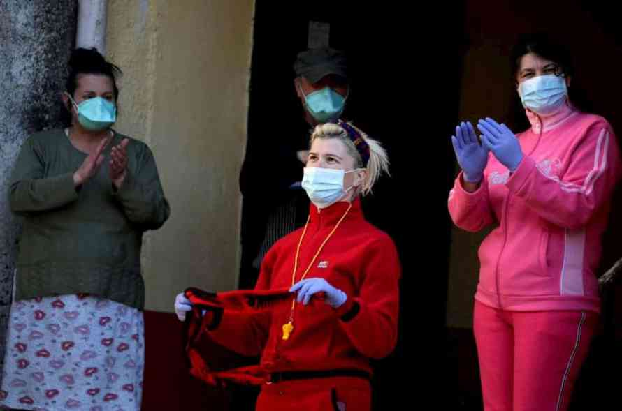 Albanian people react as a singer performs during a concert for people in home confinement as Albanian authorities take measures to stop the spread of the coronavirus disease (COVID-19) in Durres, Albania April 7, 2020. REUTERS/Florion Goga