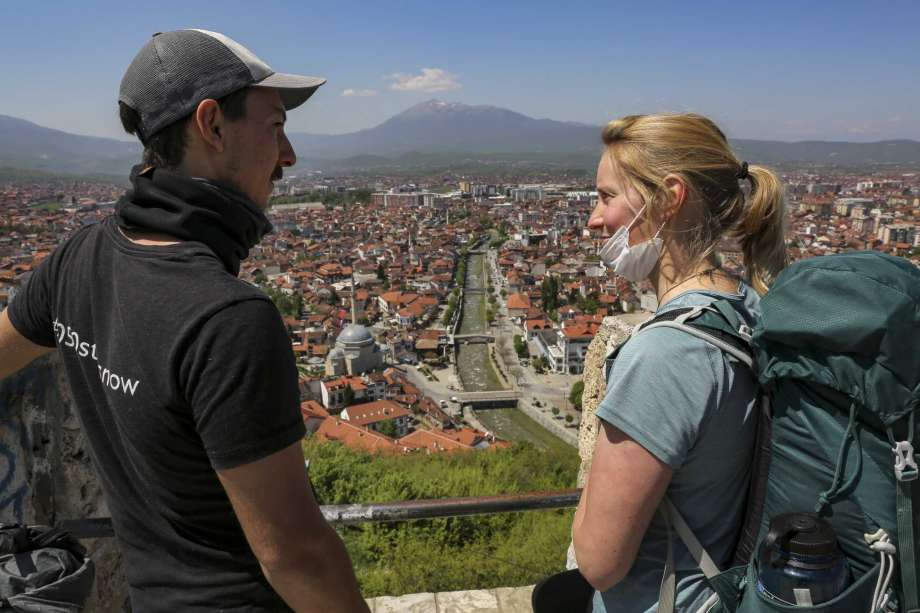 In this photo taken on Friday, April 24, 2020, Rosie Watson and Mike Elm visit the medieval fortress in Prizren, Kosovo. British climate activists Rosie Watson and Mike Elm were on an international bicycle and running tour to promote their campaign when they got stuck in Kosovo because of the coronavirus pandemic. Watson, 25, from Loweswater in northwestern England, and Mike Elm, 32, from Edinburgh, Scotland, have been stranded in Prizren, a town in Kosovo, 85 kilometers (50 miles) southwest of the capital Pristina. Since mid-March, Kosovo has been in a lockdown with all of its land and air border crossings shut. The virus has killed at least 22 people and there are more than 780 confirmed cases