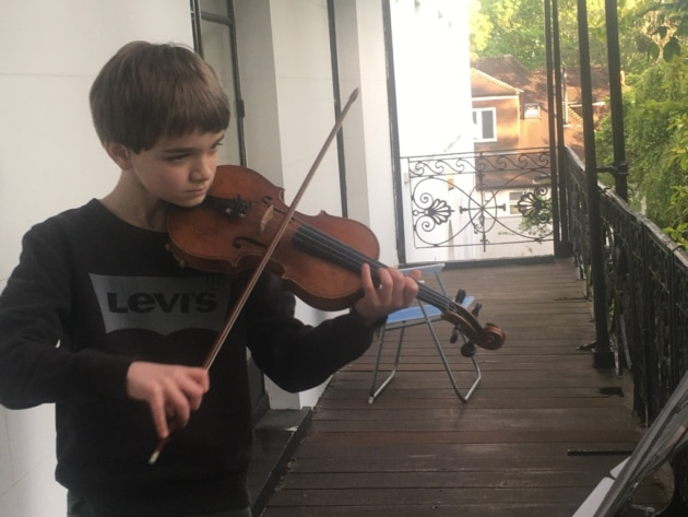 Thomas Ormond, 11, playing the violin on his balcony. He says he'll continue raising money for the NHS throughout lockdown. Picture: Ormond family