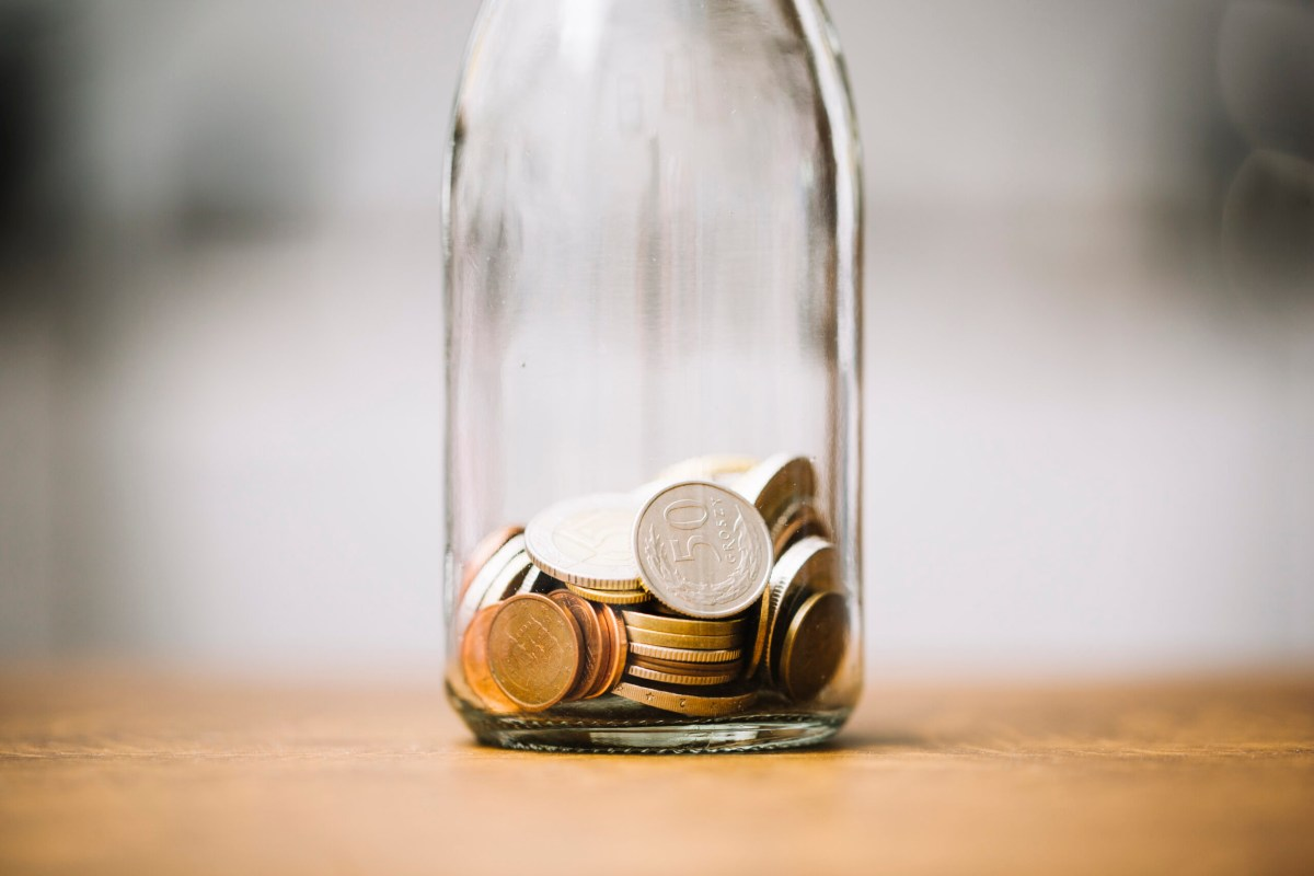 coins-glass-bottle-wooden-surface