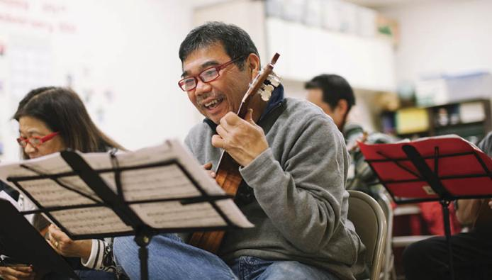 Harlan Kawamoto plays along with the music at the Ukulele Club of Chinatown in San Francisco