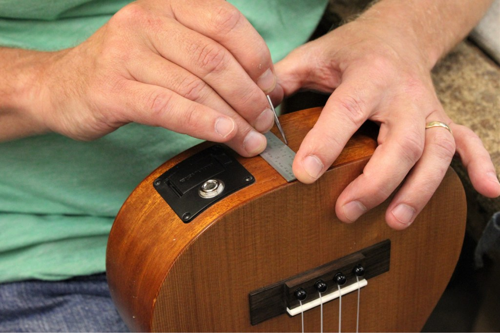 how to install a ukulele strap, marking the center of the end of the ukulele