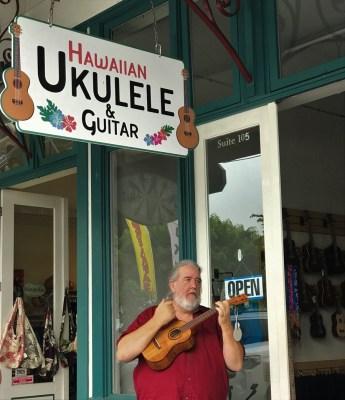 """""""Uncle Uke"""" Robert Yates playing ukulele in front of his store, Hawaiian Ukulele & Guitar"""