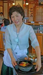 A worker at Gogung Restaurant proudly displays their best dishes.