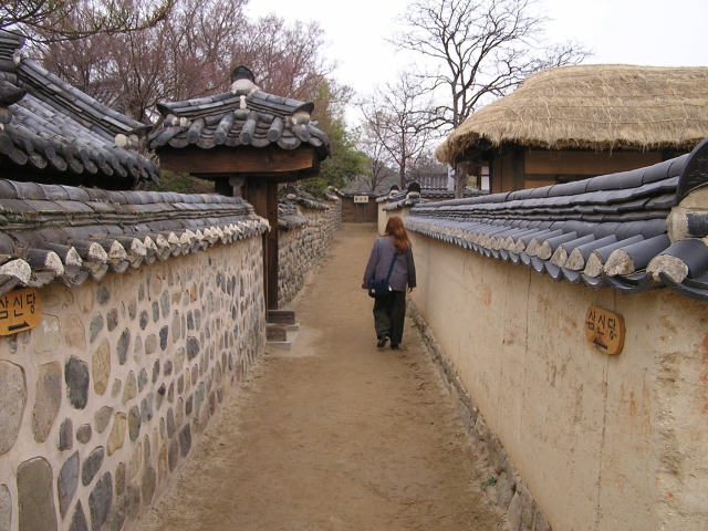 A long alleyway between homes, some with grass roofs, some with tile