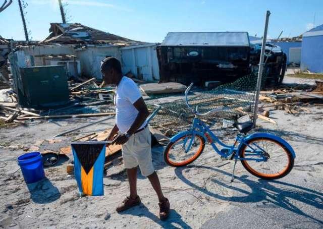 Un habitant des Bahamas marche parmi les décombres, le drapeau national à la main, sur l'île Abaco, le 11 septembre 2019.