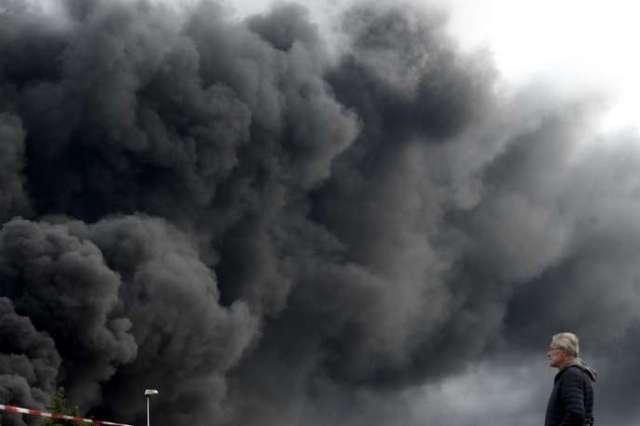 Un habitant du Petit-Quevilly, le 26 septembre face au panche de fumée provoqué par l'incendie de l'usine Lubrizol.