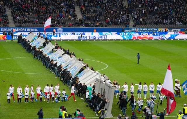 Des supporteurs de football font tomber une imitation en carton du Mur de Berlin, avant le début de la rencontre entre le Hertha Berlin et Leipzig, samedi 9 novembre.