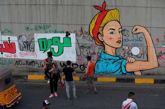 Des manifestants se tiennent à proximité d'un mur où est tagué la «Révolution des jeunes»,à Bagdad, le dimanche 3 novembre 2019.