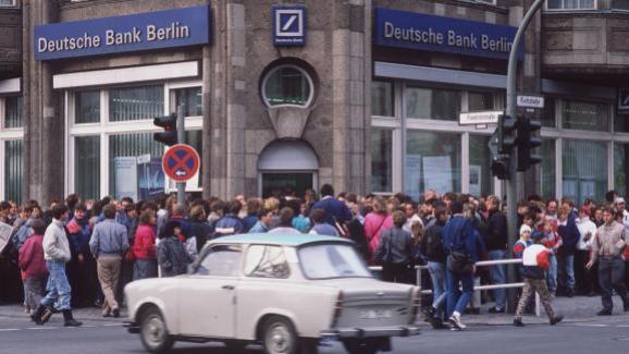 Des Allemands de l\'Est patientent devant une banque afin d\'obtenir 100 Marks de bienvenue, le 10 novembre 1989.